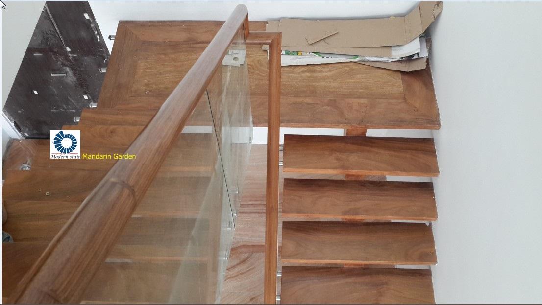 Khung cầu thang xương cá thép hộp 100x100mm ốp gỗ phủ. mặt bậc dầy 50mm gỗ lim nam phi. kính temper 12mm, liên kết đầu bậc bằng phụ kiện kính chuyên dụng, tay vịn tròn D65mm gỗ lim nam phi xẻ rãnh âm kính