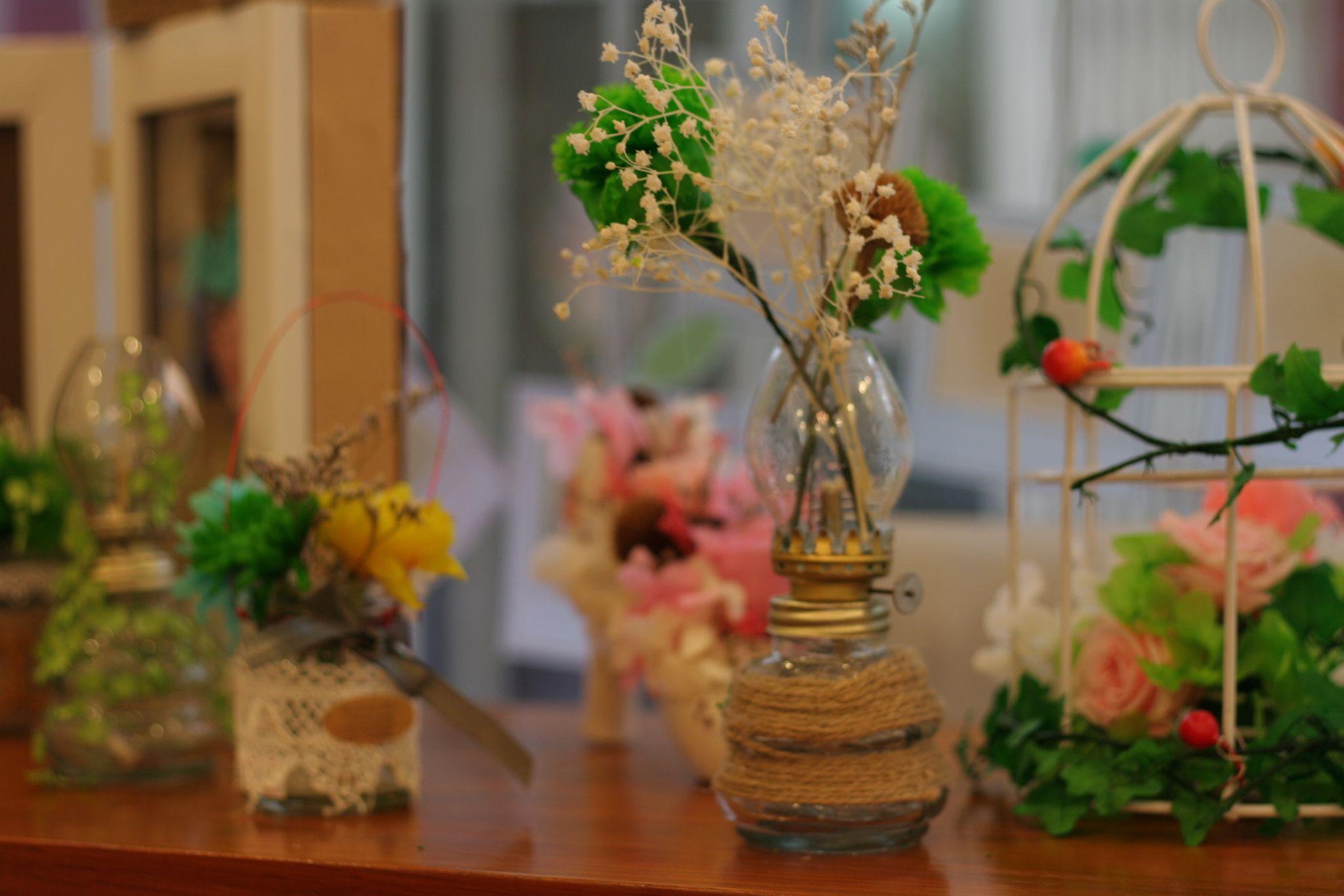 Hoa Cẩm Chướng được cắm vào đèn dầu cổ trang trí cafe
