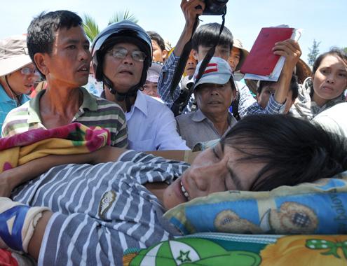 Thuyền trưởng Hải bị phía Trung Quốc đánh trọng thương được đưa từ tàu cá ở cảng Tịnh Kỳ lên xe cấp cứu trưa 18/5. Ảnh: Trí Tín.