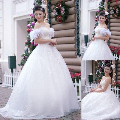 Váy xếp ngực đính pha lê với tay vai buông hờ hững kết bằng lông ngỗng, chân váy lấp lánh ánh tuyết.