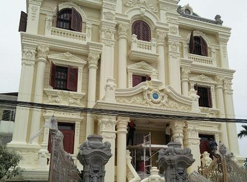 Mặt tiền chính của biệt thự được trang trí cầu kỳ với biểu tượng ngọc xanh đang chờ đợi cửa đại sảnh hoàn thiện để khoe hết sự đẳng cấp của gia chủ