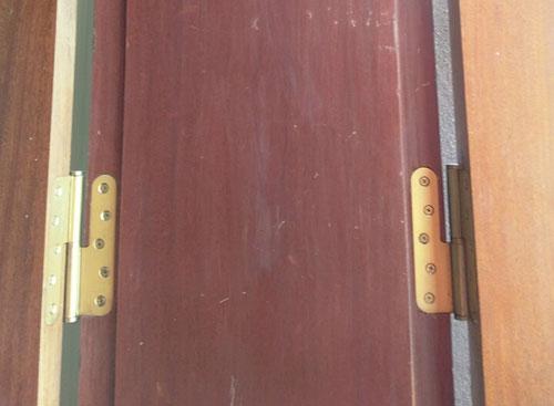 Bản lề titan tròn Sevendays nổi bật trên cánh cửa gỗ lim