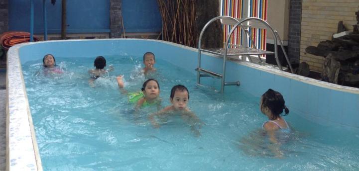 Các bé bơi ở bể bơi của trường