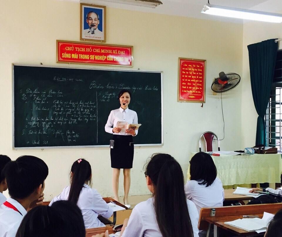 Giáo viên dùng máy trợ giảng đứng giảng dạy