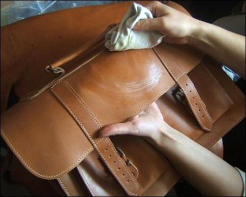 Lau chùi cặp da nam bằng khăn ẩm thường xuyên để loại bỏ bụi bẩn và mồ hôi