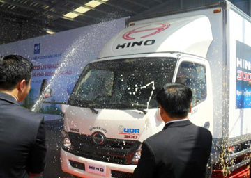 Xe Hino 300 series mới xuất hiện từ phía sau sân khấu dưới ánh sáng và champagne trong sự ngỡ ngàng của khách mời